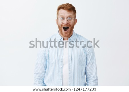 Friends bought me new car, wow. Amazed and thrilled joyful redhead man with beard in glasses and shirt, dropping jaw from amazement and happiness, smiling broadly and gazing at camera fascinated