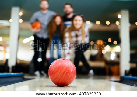 Friends bowling at club and having fun playing casually