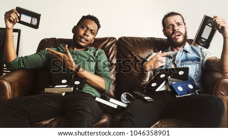 Stock Photo Friends carrying video tapes
