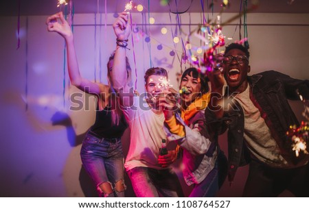 Friends celebrating and playing with fire sparkles at a house party. Young men and women having fun at a colorful house party with decorations and confetti all around.