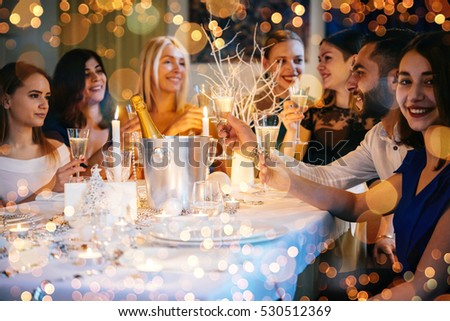 Friends celebrating Christmas or New Year eve. Party table with champagne. #530512369