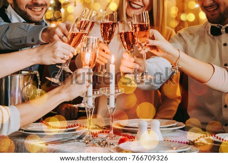 Friends celebrating Christmas or New Year eve. Party table with lights and rose champagne. #766709326