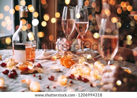 Friends celebrating Christmas or New Year eve. Party table with rose champagne.