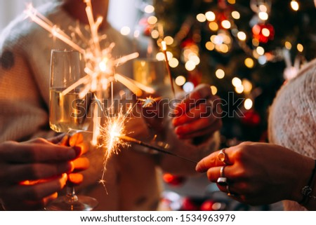 Friends celebrating Christmas or New Year eve party with Bengal lights and champagne.