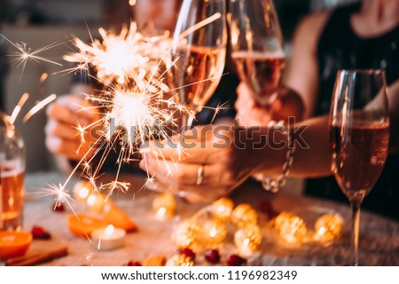 Friends celebrating Christmas or New Year eve party with Bengal lights and rose champagne. #1196982349