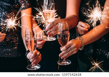 Friends celebrating Christmas or New Year eve party with Bengal lights and rose champagne. #1197142618