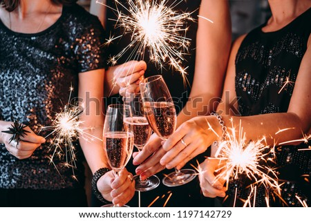 Friends celebrating Christmas or New Year eve party with Bengal lights and rose champagne. #1197142729