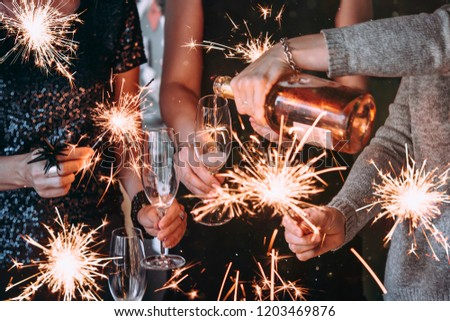 Friends celebrating Christmas or New Year eve party with Bengal lights and rose champagne. #1203469876