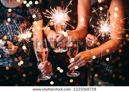 Friends celebrating Christmas or New Year eve party with Bengal lights and rose champagne. #1225068718