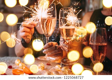 Friends celebrating Christmas or New Year eve party with Bengal lights and rose champagne. #1225068727
