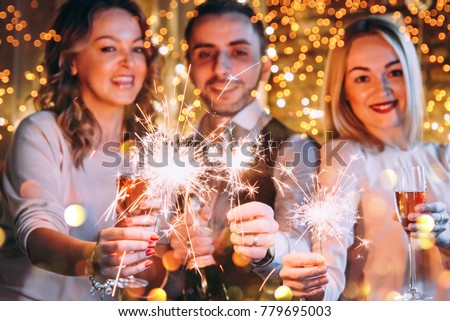 Friends celebrating Christmas or New Year eve with Bengal lights. #779695003