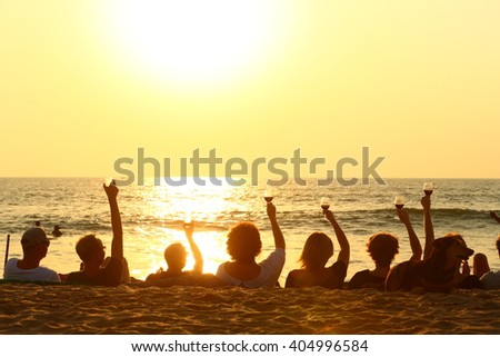 friends celebrating on a beach/ friendship/ friends celebrating on a beach in the sunset