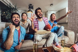 Friends cheering sport league together on tv and celebrating victory at home.Friendship, sports and entertainment concept.