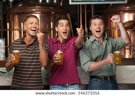 Friends cheering. Three happy soccer fans drinking beer at the pub