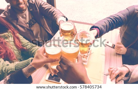 Friends cheering with beer glasses sitting around cafe bar table - Group of multiracial people toasting and clinking drinks at each others health inside pub - Vintage nostalgic old times filter look