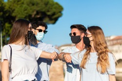 friends  cheers with elbows - four young persons say hello in the time of coronavirus