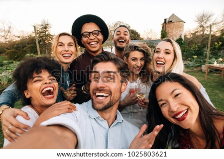Friends chilling outside taking group selfie and smiling. Laughing young people standing together outdoors and taking selfie.