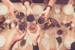 Friends clinking glasses above dinner table