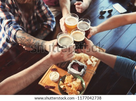 Friends clinking glasses with beer in pub
