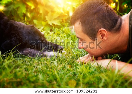 Friends concept. Man and labrador retirever dog are lying in summer grass