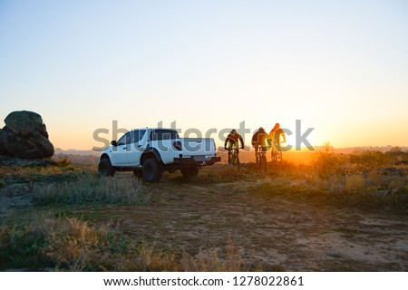 Friends Cyclists Riding Enduro Bikes in the Mountains in front of the Pickup Off Road Truck at Warm Autumn Sunset. MTB Adventure and Car Travel Concept.