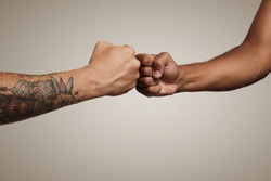 Friends do a fist bump close up isolated on white
