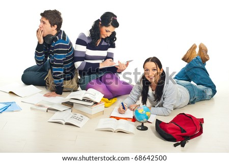Friends doing their homework together and sitting on floor - stock photo