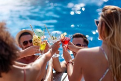 Friends drink cocktails by pool side on summer vacation and have fun together. People, love, summer, vacation and lifestyle concept.