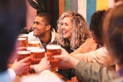 Friends drinking and toasting with beer at pub brewery - Beautiful smiling multiracial people cheering with pint of beer - Lifestyle and drink concepts in London