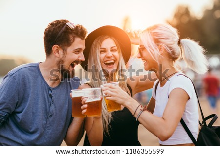 Friends drinking beer and having fun at music festival  #1186355599