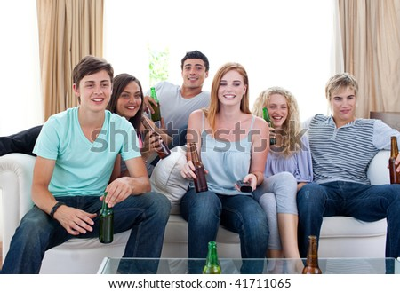 Friends drinking beer and watching tv at home