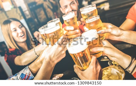 Friends drinking beer at brewery bar restaurant on weekend - Friendship concept with young people having fun together toasting brew pint on happy hour at pub - Focus on glass - Bright contrast filter