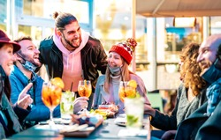 Friends drinking cocktails at bar restaurant outside - New normal nightlife concept with happy people having fun together with open face mask - Bright vivid filter with focus on woman in middle frame