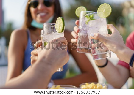 Friends drinking cocktails in an outdoors snack bar restaurant in the summer wearing face mask on to be protected from coronavirus - Happy people cheering with mojito and having fun