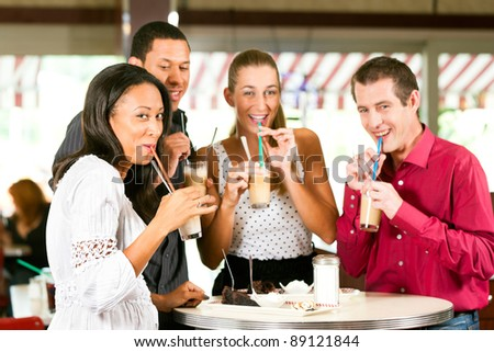 Friends drinking milk coffee and eating cake in a bar or Cafe