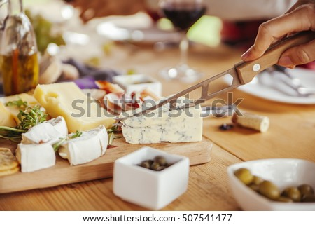 Friends Drinking Wine And Eating Cheese