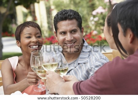 Friends drinking wine outdoors, head and shoulders