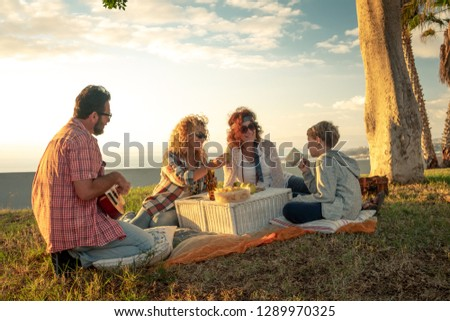 Friends eat on meadow happy young blond and curly woman with plaid shirt plays guitar brunette friend with headband smiles singing man with beard drinks bottle of beer and blond child looks amused