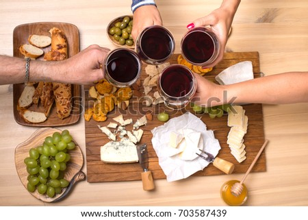 Friends eating cheese with grapes and drinking wine at home together, cheese party concept.