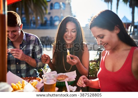 friends eating french fries and hamburgers together at outdoor restaurant under summer sun #387528805
