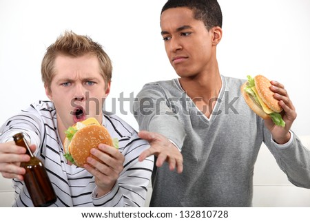 Friends eating hamburgers and watching a football game