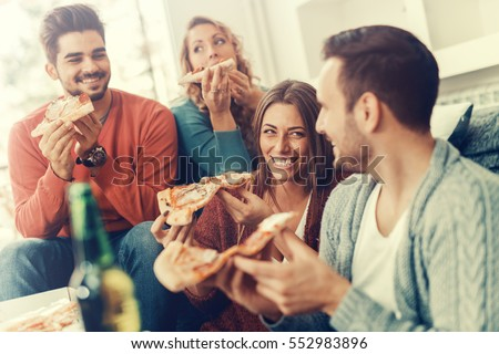 friends eating pizza.they are...