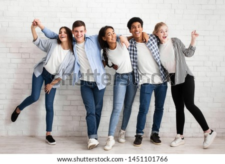 Friends embracing and having fun over white brick wall, posing to camera