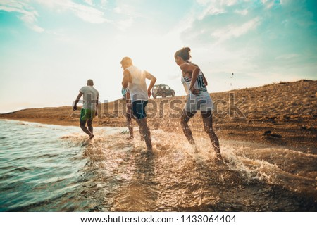 Friends enjoying on summer vacation while running through the water #1433064404