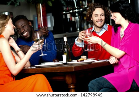 Friends enjoying snacks with drinks in a bar.
