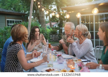 Friends enjoying summer barbecue dinner in garden