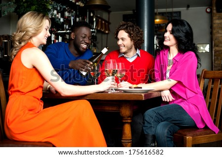 Friends enjoying their dinner with drinks at a restaurant