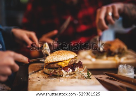 Friends enjoying together in delicious taste of burgers.
