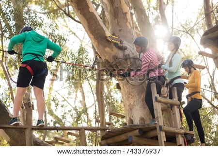 Friends enjoying zip line adventure in park on a sunny day
