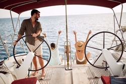 Friends excited by the trip with a yacht ona wonderful sunny day